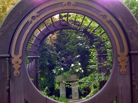 The round components in the gates frame a sculptural element - classic garden design choice.